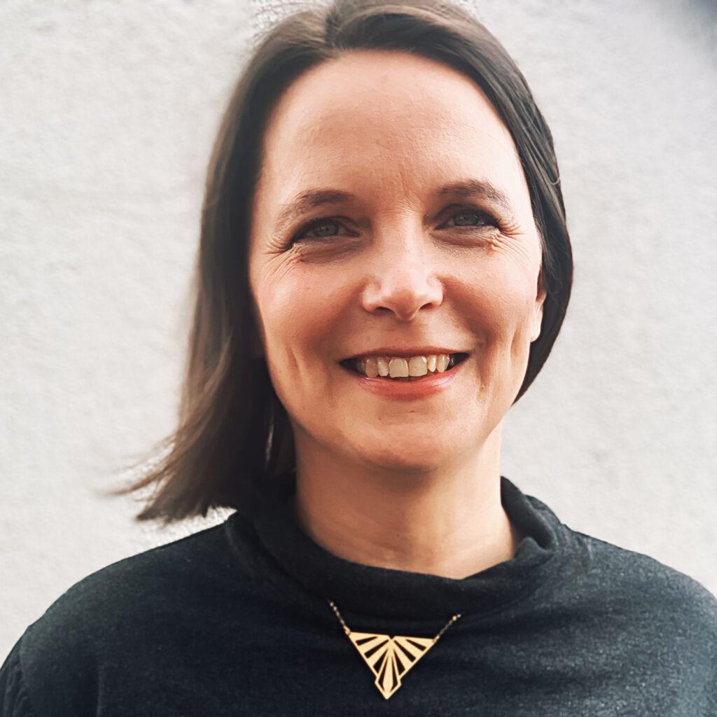 Portrait von Sarah Manteufel. Sie hat halblange braune Haare und lacht.