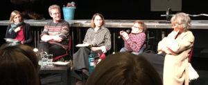 Vier Frauen und ein Mann sitzen nebeneinander auf einer Bühne. Eine Frau sitzt in einem Rolllstuhl und spricht in ein Mikrofon, die anderen schauen sie an.