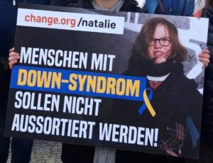 Plakat mit der Aufschrift: change.org/natalie - Menschen mit Down-Syndrom sollen nicht aussortiert werden! Hinter der Schrift liegt ein Foto von einer jungen Frau mit mittellangen dunkelblonden Haaren, dunkler Brille und Down-Syndrom.
