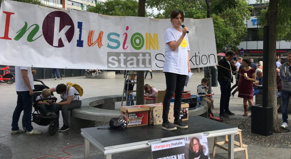 Ein Frau steht auf einem Podest und spricht in ein Mikrofon. Hinter ihr hängt ein großes Banner mit der Aufschrift: Inklusion statt Selektion