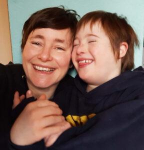 Eine Frau mit dunklen kurzen Haaren lacht und schmiegt den Kopf an ein lachendes Kind mit dunklen kurzen Haaren und Down-Syndrom.